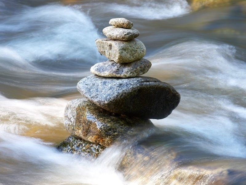 Cairn of rocks balanced in rushing river