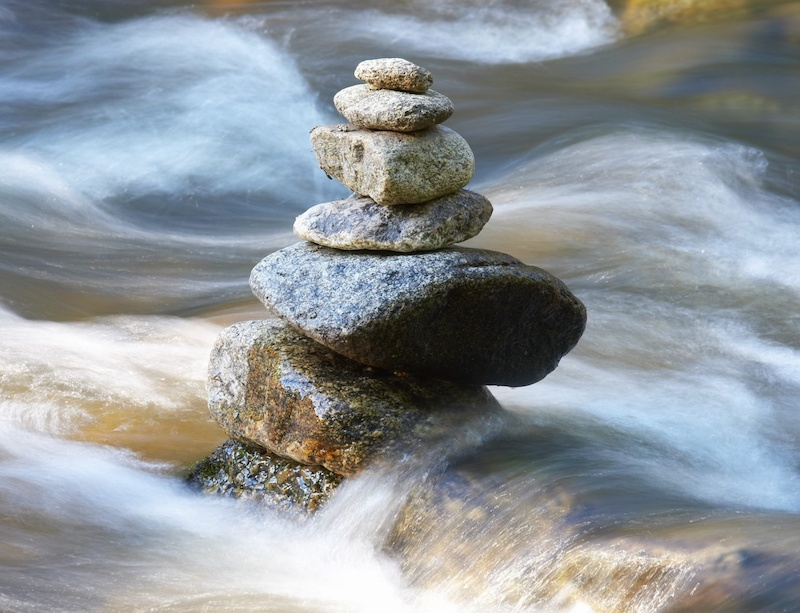 Cairn balanced in rushing river