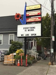 Hardware sign that says: Everything Is Weird. We are Open.""