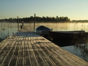 Wooden pier on misty lake with two rowboats beside it.